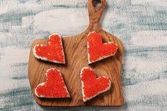 Sandwiche mit rotem Kaviar- und Frischkäse in Form eines Herzens für Valentinstag stockfoto