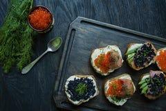 Sandwiche mit rotem und schwarzem Kaviar Nahaufnahme Dunkler h?lzerner Hintergrund stockfotos