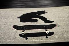 Sandwiched skateboard. Skateboard in between shadows of a boy skateboarding Stock Photography
