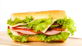 Sandwiches. Big sandwich with fresh vegetables on wooden board stock photography