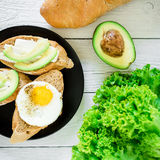 Sandwiches with avocado and egg on a dark plate on rustic background. Flat lay. Top view. Tasty breakfast for vegan Stock Photo