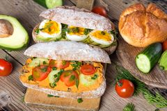 Sandwiches with avocado, eggs and tomato on a wooden background. Stock Image