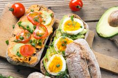 Sandwiches with avocado, eggs and tomato on a wooden background. Royalty Free Stock Image