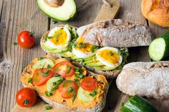 Sandwiches with avocado, eggs and tomato on a wooden background. Royalty Free Stock Photos