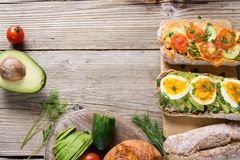Sandwiches with avocado, eggs and tomato on a wooden background. Royalty Free Stock Photo