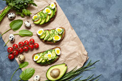 Sandwiches with avocado, spinach, guacamole, arugula and quail eggs on parchment on a concrete background. Spring food Stock Images