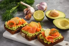 Sandwiches with avocado spread and smoked salmon. Sandwiches with avocado spread and smoked salmon royalty free stock images