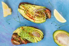 Sandwiches with avocado, sprouts, tomato, blue background, top v Royalty Free Stock Images