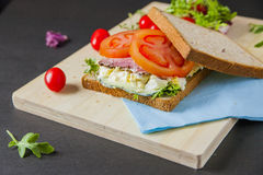 Sandwiches. Bacon, lettuce, Broken egg salad and tomato sandwiches with fresh tomato and lettuce on the wooden board Royalty Free Stock Photo