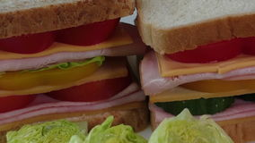 Sandwiches with bacon, salami, prosciutto and fresh vegetables stock footage