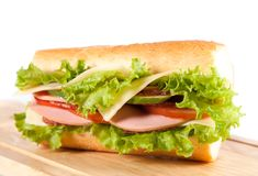 Sandwiches. Big sandwich with fresh vegetables on wooden board royalty free stock image