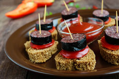 Sandwiches with black rye bread in the shape of a heart, blood sausage Morcillo and pieces of sweet pepper on skewers. In a ceramic bowl with tomato sauce on a stock images