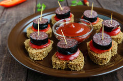 Sandwiches with black rye bread in the shape of a heart, blood sausage Morcillo and pieces of sweet pepper on skewers. In a ceramic bowl with tomato sauce on a stock photo