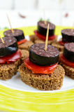 Sandwiches with black rye bread in the shape of a heart, blood sausage Morcillo and pieces of sweet pepper on skewers. And tomato sauce, on a white wooden royalty free stock photos