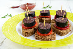 Sandwiches with black rye bread in the shape of a heart, blood sausage Morcillo and pieces of sweet pepper on skewers. And tomato sauce, on a white wooden stock photo
