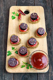 Sandwiches with black rye bread in the shape of a heart, blood sausage Morcillo and pieces of sweet pepper on skewers,. Tomato sauce on a dark wooden background stock photo