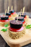 Sandwiches with black rye bread in the shape of a heart, blood sausage Morcillo and pieces of sweet pepper on skewers. Tomato sauce on a dark wooden background stock images