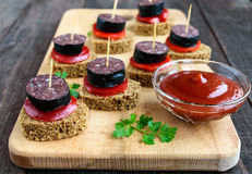Sandwiches with black rye bread in the shape of a heart, blood sausage Morcillo and pieces of sweet pepper on skewers,. Tomato sauce on a dark wooden background stock photos
