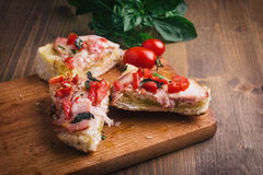 Sandwiches on a board on a wooden table. Sandwiches with tomato, ham and cheese, on a board on a wooden table Stock Photography