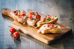 Sandwiches on a board on a wooden table. Sandwiches with tomato, ham and cheese, on a board on a wooden table Royalty Free Stock Photography