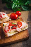 Sandwiches on a board on a wooden table. Sandwiches with tomato, ham and cheese, on a board on a wooden table Stock Image