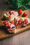 Sandwiches on a board on a wooden table. Sandwiches with tomato, ham and cheese, on a board on a wooden table Stock Images