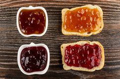Sandwiches and bowls with currant jam, apricot jam on table. Top view. Sandwiches and bowls with currant jam, apricot jam on dark wooden table. Top view stock photography