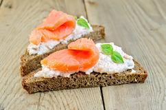 Sandwiches on bread with salmon and basil on board Royalty Free Stock Photo