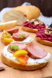 Sandwiches for breakfast with fried sausages, yellow tomatoes, creamy mustard sauce on a cutting board. stock photography