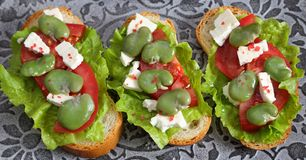 Sandwiches  with broad bean. Sandwiches with broad beans, tomatoes and goat cheese royalty free stock image