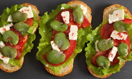 Sandwiches  with broad bean. Sandwiches with broad beans, tomatoes and goat cheese. Salad in a bowl stock photography