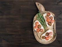 Sandwiches of brushetta met geroosterde kersentomaten, zachte kaas, Stock Afbeelding