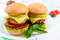 Sandwiches burgers with yellow and black tomatoes, juicy cutlet, avocado Royalty Free Stock Photos