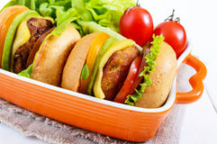 Sandwiches burgers with yellow and black tomatoes, juicy cutlet, avocado Royalty Free Stock Image