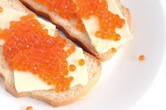 Sandwiches with butter and red caviar on white bread lies on a round plate, isolated over white Stock Photos