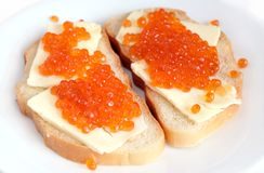 Sandwiches with butter and red caviar on white bread lies on a round plate, isolated over white Stock Image