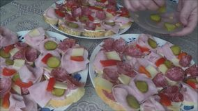 Sandwiches (canapes) of salami on a plate stock video