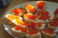 Sandwiches with caviar. Sandwiches with red caviar and butter on a white plate Stock Images