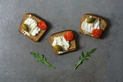 Sandwiches with cheese, cherry tomatoes and capers on a gray surface. Sandwiches with cheese, cherry tomatoes and capers on a gray surface Royalty Free Stock Image