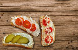 Sandwiches with cheese, cherry tomatoes and cucumbers with cottage cheese paste on a wooden table stock photos
