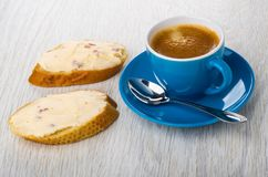 Sandwiches with cheese, coffee in cup, spoon on saucer on table stock image