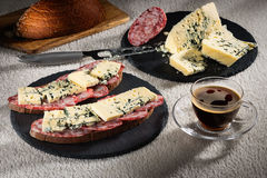 Sandwiches with cheese of Dorblu and raw smoked sausage on black slate plates, a cheese knife and a cup of hot coffee. Sandwiches with cheese of Dorblu and raw Royalty Free Stock Image