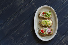 Sandwiches with cheese, egg, radish, cucumber and tomatoes. On dark wooden surface Royalty Free Stock Photos