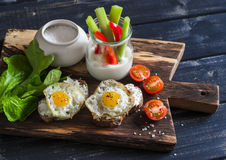 Sandwiches with cheese and fried quail eggs, fresh herbs and cherry tomatoes, Greek yogurt, celery and pepper. Healthy breakfast o Stock Photos
