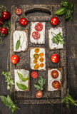 Sandwiches with cheese tomatoes fresh herbs on a wooden cutting board on rustic wooden background top view homemade Stock Images