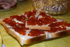 Sandwiches consist of bread, oil, red caviar. Sandwiches are located on a plate royalty free stock photos