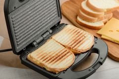 Sandwiches cooked in panini press. Sandwiches, cooked in a panini press. Snacks for lunch with grilled bread crust and yummy Cheddar cheese filling stock photos