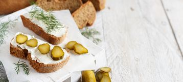 Sandwiches with cream cheese, dill and salted cucumber. On a wooden table Stock Images