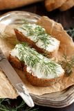 Sandwiches with cream cheese and fresh dill. On a wooden table Stock Photos