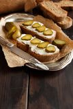 Sandwiches with cream cheese and salted cucumber. On a wooden table Stock Images